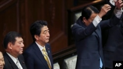 Japanese Prime Minister Shinzo Abe, center left, Minister in charge of regional issues Shigeru Ishiba, second left, listen as lawmakers of the House of Representatives shout a banzai cheer after the parliament was dissolved for a general election in Tokyo