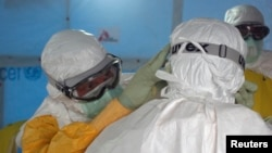 A U.S. doctor in a protective suit in Liberia adjust that of a colleague before entering an Ebola treatment unit in Monrovia in this photo released Sept. 16, 2014.