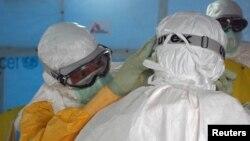 Một bác sĩ Mỹ trong trang phục bảo hộ PPE giúp đồng nghiệp điều chỉnh lại bộ bảo hộ trước khi đi vào một đơn vị điều trị Ebola ở Monrovia, Liberia.