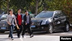 三名青年走过北京一家凯迪拉克汽车销售点。(资料照片)