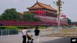 帶著孩子的婦女站在北京天安門廣場為中共建黨100週年的紀念活動做準備而豎起的路障前。(2021年6月23日)