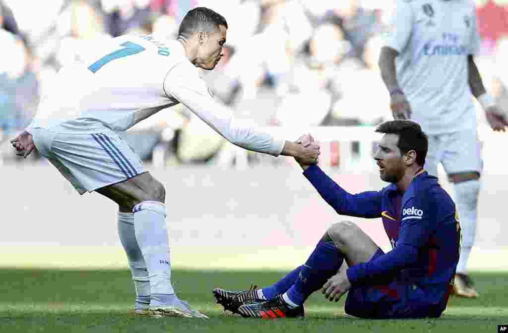 Cristiano Ronaldo du Real Madrid, aide le Barcelonais Lionel Messi à se remettre sur pied lors du match de football de la Liga espagnole entre le Real Madrid et Barcelone à Madrid, le 23 décembre 2017.