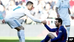 Christiano Ronaldo aidant Leonel Messi à se relever lors du classico de la Liga entre le Real Madrid et Le FC Barcelone à Santiago Bernabeu, Madrid, 23 Décembre 2017 (AP Photo/Francisco Seco)