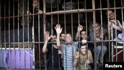 FILE - Inmates gesture from behind bars in Aleppo's main prison May 22, 2014. A recent coalition airstrike on an IS-run prison in the eastern Syrian town of al-Mayadeen reportedly killed 57 people.