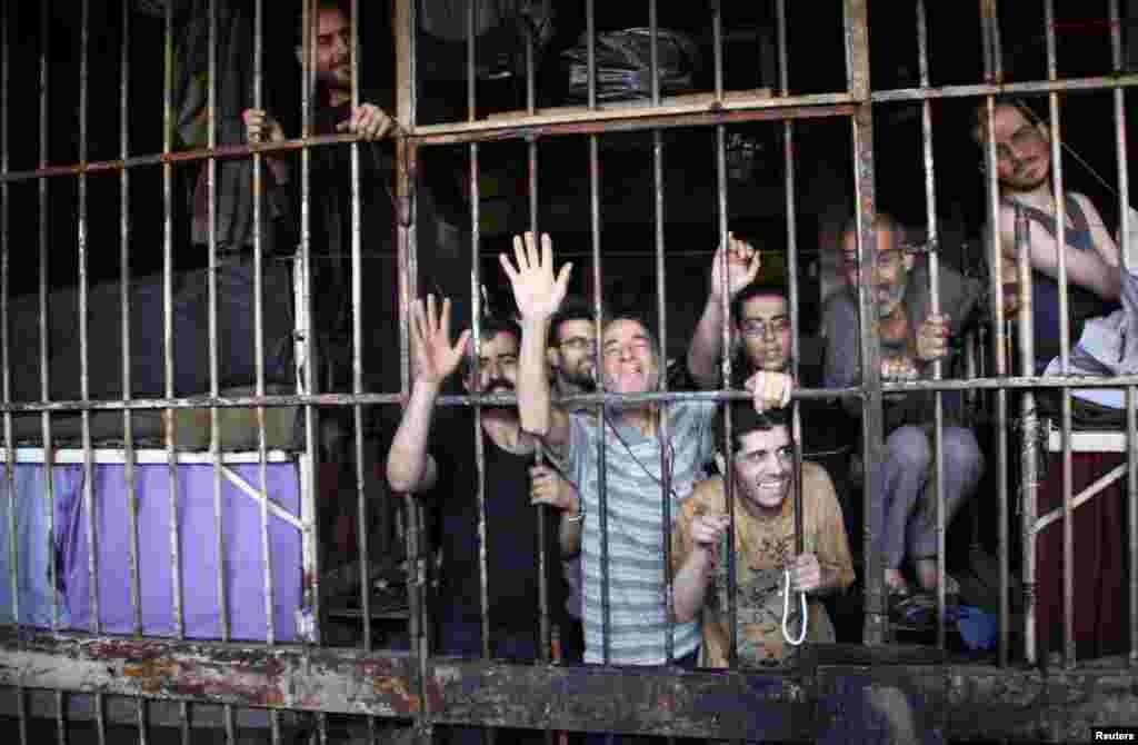 Inmates gesture from behind bars in Aleppo's main prison, May 22, 2014.