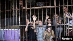 Inmates gesture from behind bars in Aleppo's main prison May 22, 2014. Syrian troops have broken a year-long rebel siege on Aleppo's main prison after heavy fighting with al Qaeda fighters and other Islamist brigades, the Syrian Observatory for Human Righ