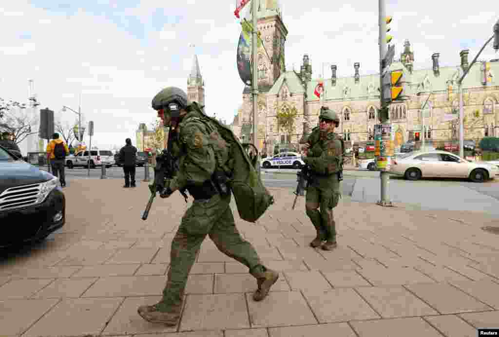Armed RCMP officers head towards the Langevin Block on Parliament Hilll following a shooting incident in Ottawa, Canada, Oct. 22, 2014.