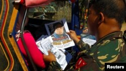 FILE - Soldiers distribute pictures of a member of extremist group Abu Sayyaf, Isnilon Hapilon, who has a U.S. government bounty of $5 million for his capture, in Butig, Lanao del Sur in southern Philippines, Feb. 1, 2017. (REUTERS/Marconi B. Navales)