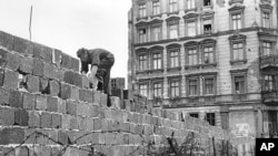 A policeman in East Berlin works on the Berlin Wall on October 9, 1961. (AP Photo/Archiv)