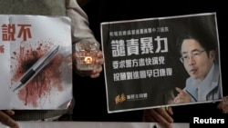 Aktivis pro-demokrasi mengangkat poster mantan redaktur surat kabar di Hong Kong, Kevin Lau menuntut polisi untuk menyelidiki penusukan terhadap redaktur tersebut.