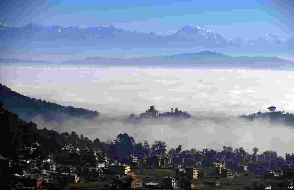 The Langtang mountain range towers over the Kathmandu Valley, hidden under a blanket of clouds, as seen from Bhanjyang on the outskirts of Kathmandu, Nepal.