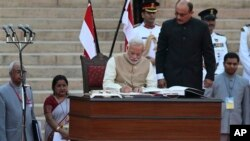 India's new prime minister Narendra Modi, center, signs after taking the oath of office at the presidential palace in New Delhi, India, Monday, May 26, 2014. Modi's inauguration is the first to which India invited leaders from across South Asia. (AP Phot