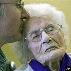 Besse Cooper, 114, right, receives a kiss from her grandson Paul Cooper, 42, during a ceremony in which Guinness World Records recognized her as the word's oldest living person - and now now hold the title of oldest living North American - at the nursing