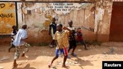 FILE - Children play in the street in Kisenyi, a slum in Kampala.