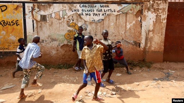 FILE - Children play in the street in Kisenyi, a slum in Kampala.