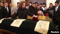 차량 폭탄 테러로 숨진 레바논의 무함마드 샤타 전 재정장관의 장례식이 29일 열린 가운데 그의 아들 오마르 샤타씨가 부친의 관 옆을 지키고 있다.