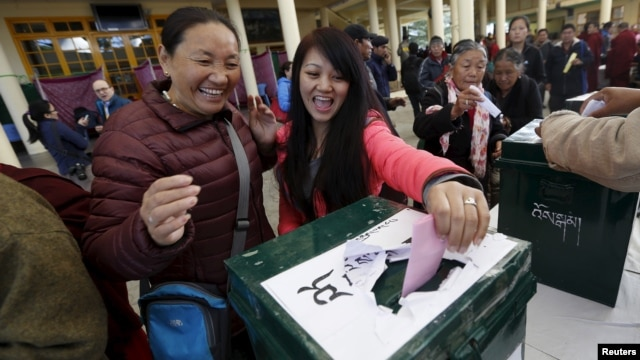 Tibetan exiles react as they cast their vote during the elections for the Tibetan government-in-exile at a polling booth in Dharamsala, India, March 20, 2016.