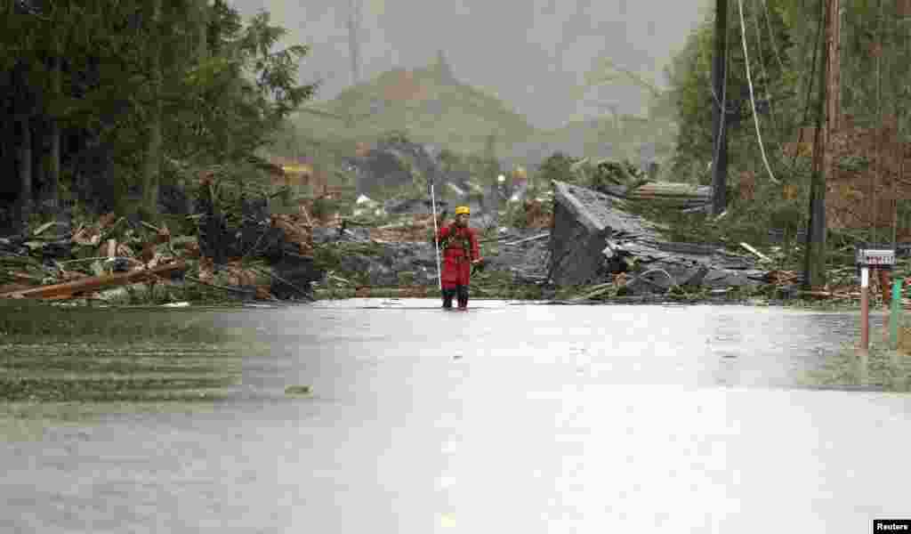 A rescuer stands on a flooded Highway 530 as search work continues in the mud and debris from a massive mudslide that struck Oso near Darrington, Washington, USA, Mar. 27, 2014.