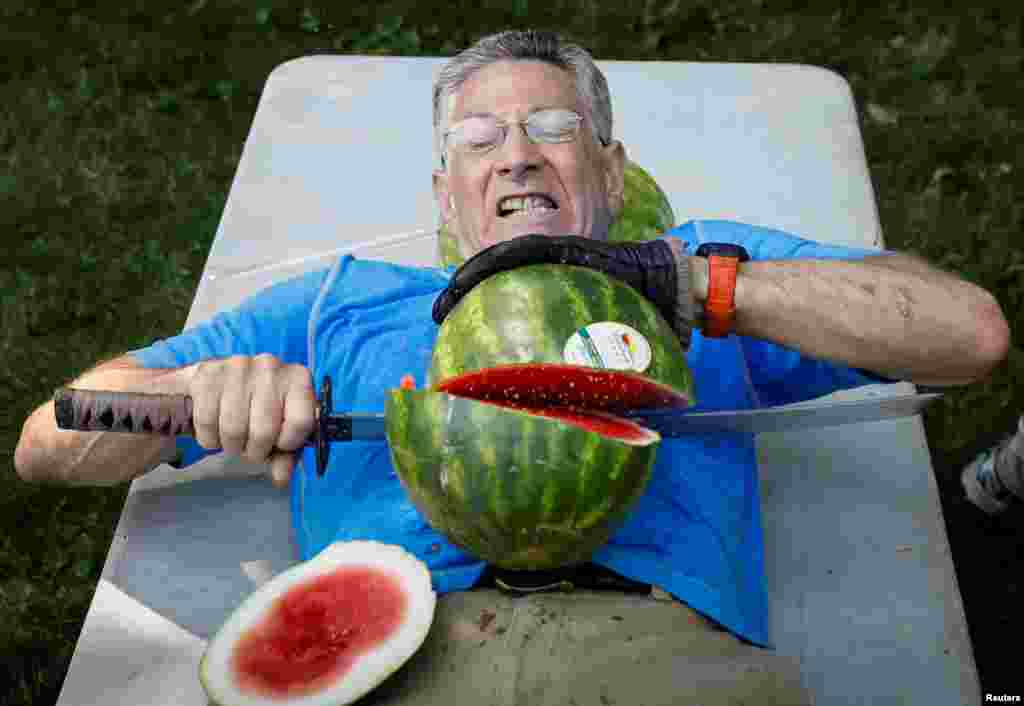 Ashrita Furman, who holds more Guinness World Records than anyone, attempts to set a new record for slicing the most watermelons in half on his own stomach in one minute in New York City, July 17, 2018.