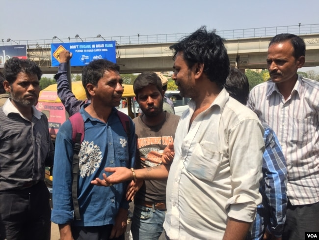 Cash shortages have eased, but Dhani Ram (in white shirt), a daily wage laborer, still finds it difficult to find work as the real estate sector continues to struggle. (A. Pasricha/VOA)