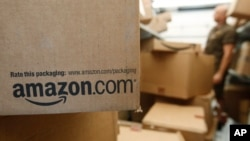 FILE - An Amazon package awaits delivery in Palo Alto, California. The online retailer is suing more than 1,000 people for advertising their services writing fake reviews.