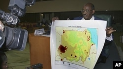 Director of the Sudanese Survey Authority Prof. Ahmad Al-Sadiq displays a new map of the country of Sudan, announced by the Sudanese Ministry of Information in Khartoum, July 4, 2011