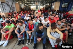 FILE - Migrants wait to disembark from the Vos Hestia ship as they arrives in the Crotone, Italy, after being rescued by a Save the Children crew in the Mediterranean sea off the Libya coast, June 21, 2017.