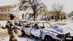 Seorang tentara Nigeria berjalan di dekat mobil yang hancur akibat ledakan bom di dekat gereja Katolik Santa Theresa di Madalla, pinggiran ibukota Abuja (25/12).