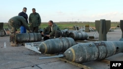 Libyan soldiers loyal to Libya's internationally recognized government work next to bombs at the Benina air base on Dec. 10, 2015, south of the eastern coastal city of Benghazi.