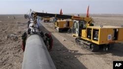 工人们在焊接经过中国甘肃省境内的天然气输送管道(资料照片)