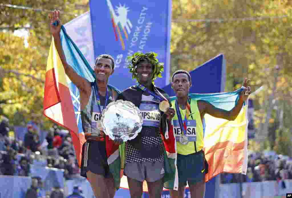 Juara putra Wilson Kipsang (tengah) beserta juara keduaLelisa Desisa Benti (kiri) dari AS, juara ketiga Gebre Gebremariam dariEthiopia, usai Maraton New York tahunan yang ke-44 di kota New York (2/11).(AP/Kathy Willens)