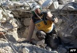 Muhaliflere bağlı Suriye Sivil Savunma ekibinden bir kişi enkaz altında kalan bir kadını kurtarmaya çalışırken