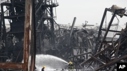 Firefighters spray foam amid twisted metal frames of a charred chemical factory, July 6, 2021 in Samut Prakan, Thailand.