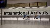 FILE - In this Jan. 26, 2021 file photo, arriving passengers walk past a sign in the arrivals area at Heathrow Airport in London, during England's third national lockdown since the coronavirus outbreak began.