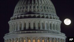 The moon rises behind the U.S. Capitol Dome as Congress works into late evening to resolve fiscal cliff issue