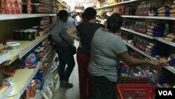 Muchos compradores pasan horas haciendo colas para poder adquirir los productos que buscan. [Foto: VOA].