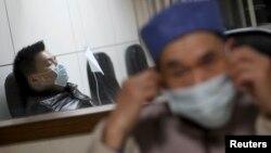 Một bệnh nhân (trái) bại sốt và được nhập viện trong tỉnh Chiết Giang để chữa trị.