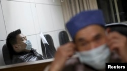 一名发烧的病人(左)4月3日在杭州一家医院接受治疗。一名67岁感染了H7N9病毒的患者也在这家医院治疗。