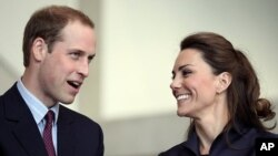 Britain's Prince William speaks, watched by his fiancee Kate Middleton at the Darwen Aldridge Community Academy, in Darwen, northern England, April 11, 2011