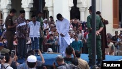 An Indonesian man charged with having gay sex is publicly caned outside a mosque in Banda Aceh, Aceh province, Indonesia, July 13, 2018.