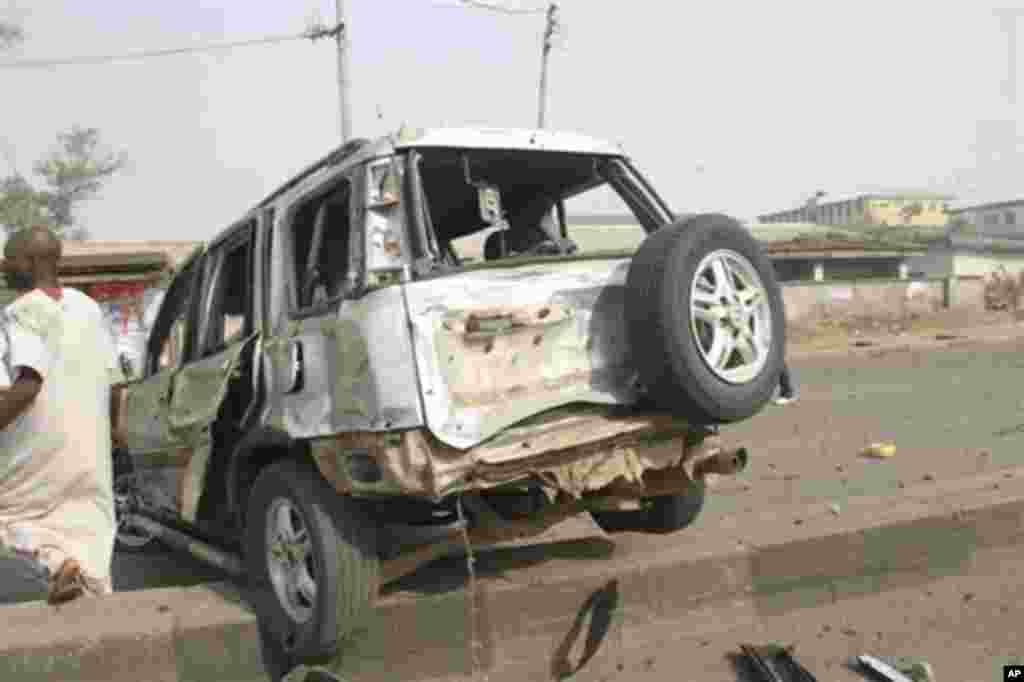Nan mutane ne 'yan kallo suka taru a inda Bom ya fashe a hanyar Kaduna, Nigeria lahadin da ta gabata, 8 ga watan nan na Afilu, 2012.
