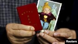 资料照:中国张家口市一家玻璃厂60岁的老工人江卫矛(音)和53岁的妻子手拿他们死亡的独生子在孩童时期的照片和独生子女证。(2015年11月21日)