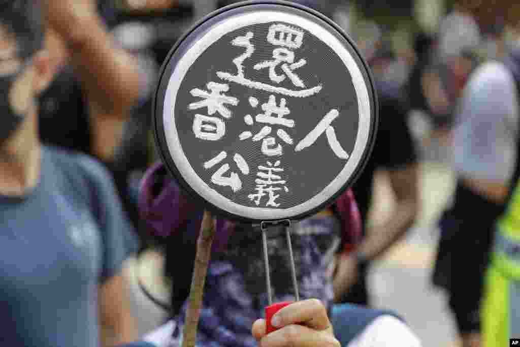 """一名示威者手持写着""""还香港人公义""""的锅具参加10月5日在港岛的抗议活动"""