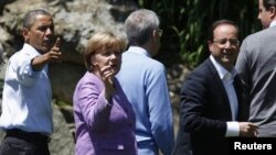 U.S. President Barack Obama, Germany's Chancellor Angela Merkel and French President Francois Hollande (L to R) face the media as the G8 leaders gather for a family photo at the G8 Summit at Camp David, Maryland, May 19, 2012