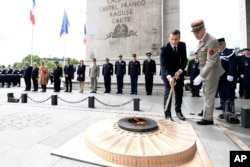 President Emmanuel Macron light up the flame on the Unknown Soldier's tomb at the Arc of Triomphe after his formal inauguration ceremony as French President in Paris, May 14, 2017.