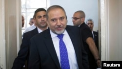 Former Israeli Foreign Minister Avigdor Lieberman (C) enters the courtroom to hear the verdict in the corruption charges against him at the Magistrate Court in Jerusalem, Nov. 6, 2013.