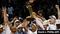 Tim San Antonio Spurs dan piala kemenangan, trofi Larry O'Brien dari NBA (15/6). (AP/David J. Phillip)
