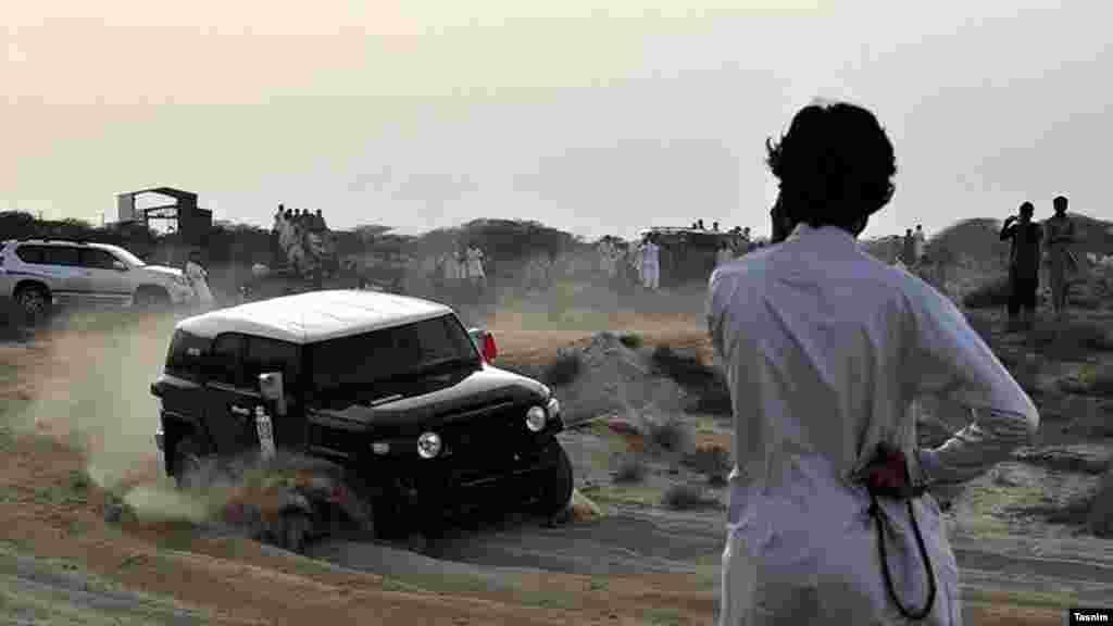 مسابقات رالی دو دیفرانسیل در منطقه ازاد چابهار و جوانی که آن را تماشا می کند. عکس: مهین محمد زاده، تسنیم