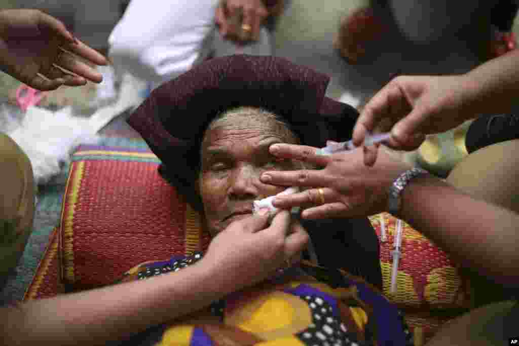 An elderly woman receives an eye treatment at a temporary shelter for villagers affected by Mount Sinabung's eruption in Kuta Rakyat, North Sumatra, Indonesia.