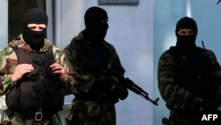 FILE - Armed men stand guard in front of the entrance of the Mejlis of the Crimean Tatar people, the single highest executive-representative body of the Crimean Tatars, in Simferopol, Sept. 16, 2014.